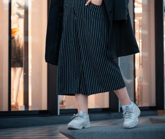 Szemüveges nő fekete culotte nadrágban és fekete kabátban egy kirakat előtt