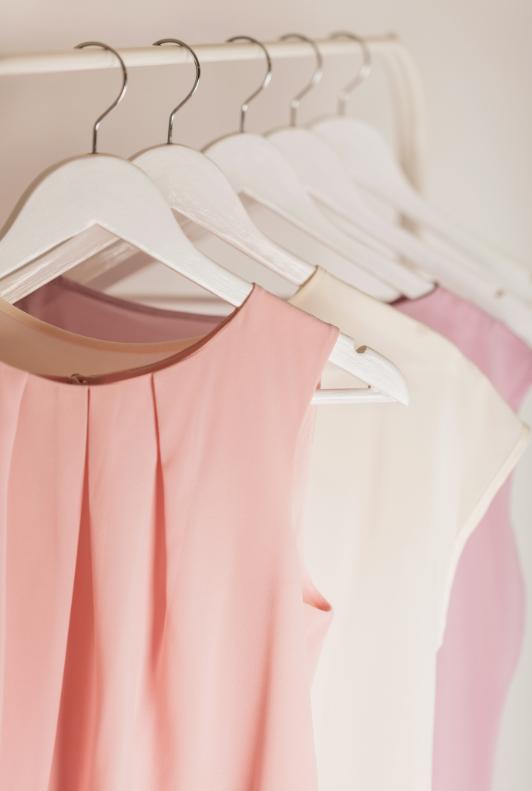 Rózsaszín és fehér ujjatlan blúzok vállfán