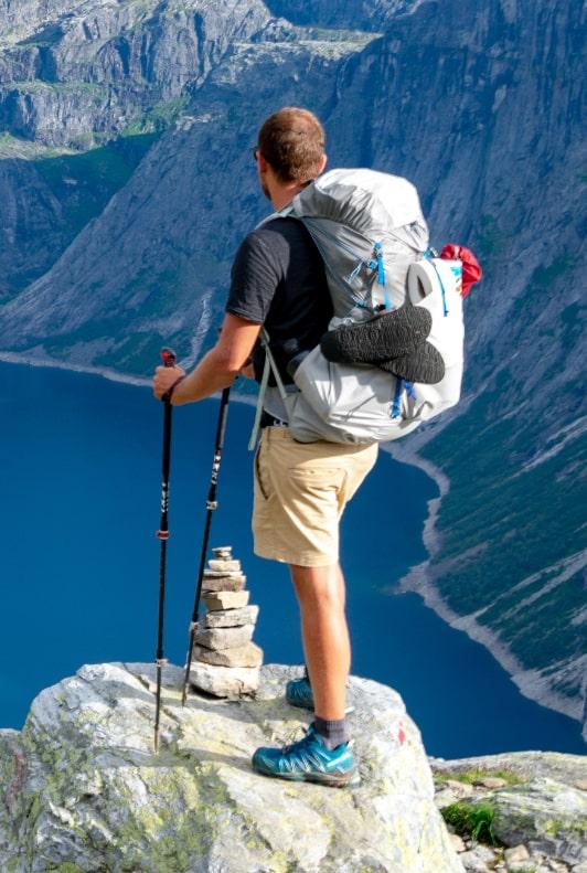 Férfi rövidnadrágban, hátizsákkal egy hegy tetején