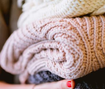 3 különböző színű, csinos női pulóver egymásra hajtogatva