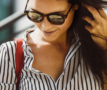 Fiatal nő fekete-fehér csíkozású ingben és napszemüvegben