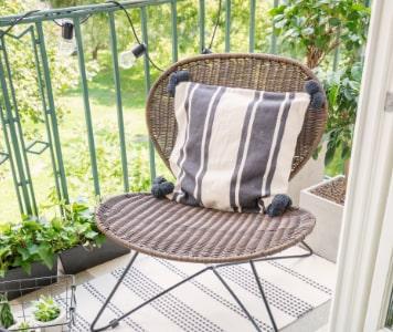 Erkély székkel, lakástextilekkel és növényekkel