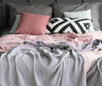 Színes párnák és takarók egy franciaágyon stílusosan elrendezve