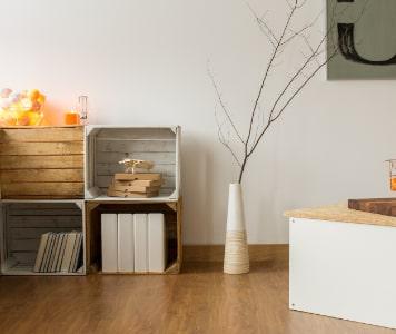 Ládákból készült polc, fehér váza faággal, fehér szőnyeg egy szobában
