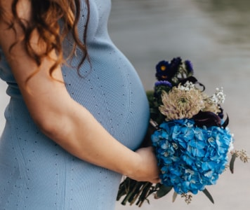 Hosszú hajú kismama világoskék alkalmi ruhában és kék-fehér virágcsokorral