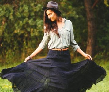 Barna hajú nő kalappal, szürke ingben és sötétkék maxiszoknyában