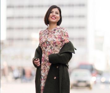 Fiatal nő virágos nyári ruhában, vastag szövetkabátban és csizmában