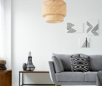 Skandináv nappaliban fehér falak, szürke kanapé, fonott lámpa, és fekete-fehér kiegészítők.