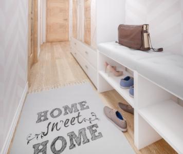 Keskeny előszoba fehér cipősszekrénnyel és feliratos szőnyeggel