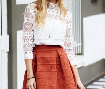 Szőke nő narancssárga miniszoknyában, fehér csipkés felsőben és fehér baseball sapkában