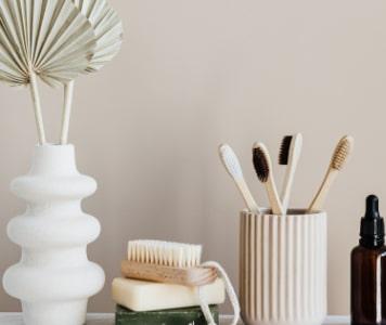 Fenntartható szappanok, kefe, bambusz fogkefe, fehér váza bézs háttér előtt