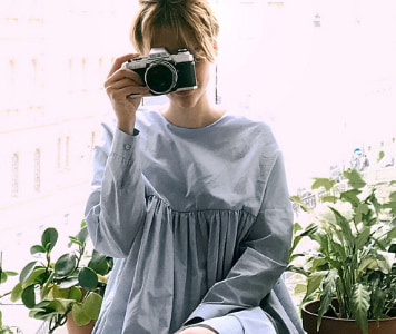 Fiatal nő világos szürkés-kék ruhában fényképezőgéppel
