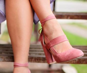 Egy pár rózsaszín bokapántos magassarkú cipő női lábon, közelről.